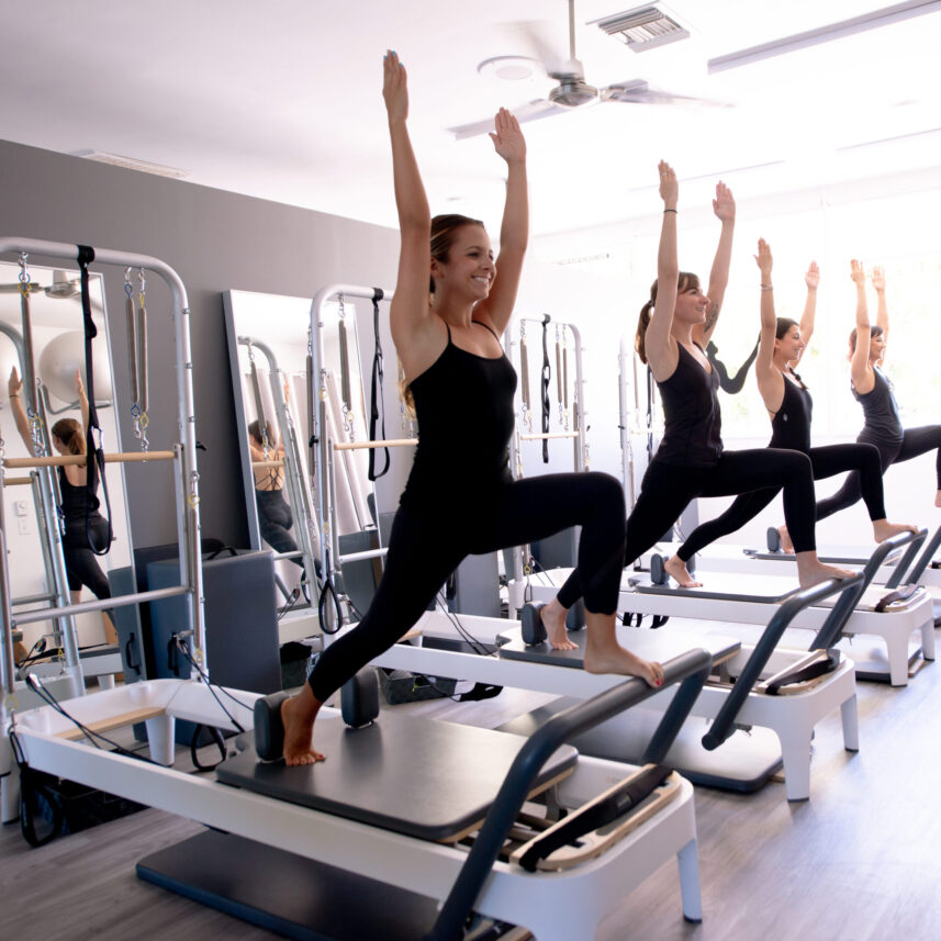 reformer class women in standing lunge modern pilates studio